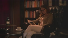Young woman reading a book while drinking tea Stock Footage