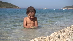Small child funny playing with stone in the sea. - stock footage