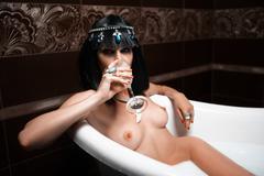 beautiful sexy woman topless takes a milk bath - stock photo