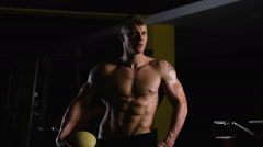 Bodybuilder on top form. Beautiful young athlete posing for a photo session - stock footage