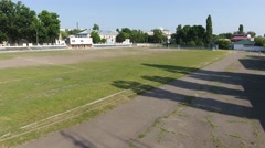 Quick camera flying over the unkempt old football field Stock Footage