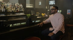4K Friendly bartender serving & chatting with young couple in trendy bar Stock Footage