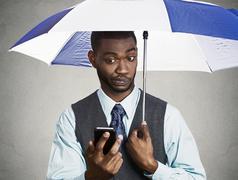 Executive man holding smart phone, reading news on a rainy day Stock Photos
