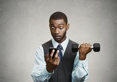 Corporate executive shocked by news on smart phone, lifting weights Kuvituskuvat