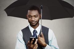 Businessman texting under umbrella - stock photo