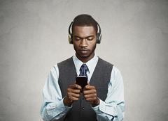 Phone addicted business man with headphones - stock photo