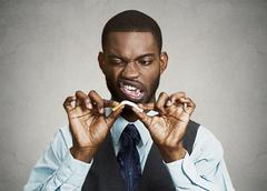 Upset angry business man breaking cigarette - stock photo