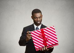 Unhappy man, displeased with new gift - stock photo
