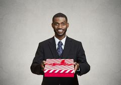 Happy businessman giving gift box to someone - stock photo