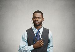 Executive man listening  to his heart, self criticism concept - stock photo