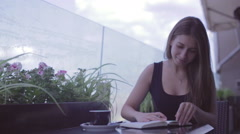 Pretty girl sitting in the street cafe and writing notes in the notebook Stock Footage
