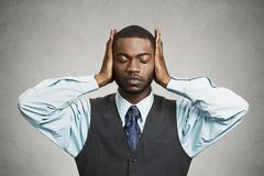 Man covers his ears, eyes closed, hear, see no evil concept - stock photo
