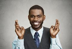 Hopeful businessman crossing his fingers Stock Photos