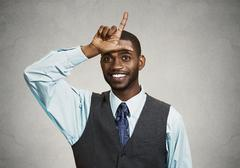 Young executive giving loser sign - stock photo