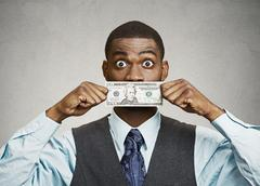 Shocked man with dollar bill curency covering his mouth Stock Photos