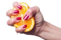 Hand with manicured nails touch an orange on white Stock Photos