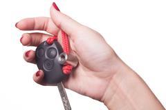 Close up of hand holding car key on white - stock photo