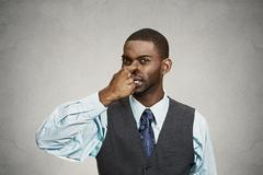 Man pinches his nose, very bad smell, odor - stock photo