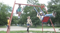 Children swinging on the swings at the playground in the park Stock Footage
