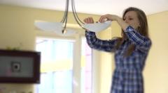 Woman screw eco light bulbs in chandelier Stock Footage