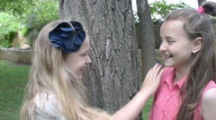 Two girls whisper in the ear of a secret - a picnic in the park Arkistovideo