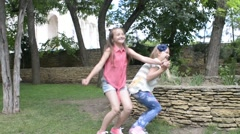 Two girls whirling , jumping and having fun in a park picnic - a happy childhood Stock Footage