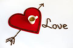 Cup of coffee on a red felt heart with arrow and love Stock Photos