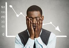Business man desperate with financial market chart graphic going down Stock Photos