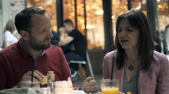 Young couple talking, eating and sharing food in cafe in the city Stock Footage