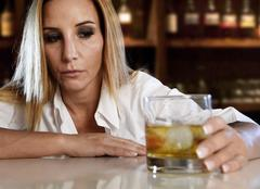 Drunk blond alcoholic woman wasted depressed at bar or pub Stock Photos