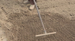 Old farmer raking the ground with the rake in the vegetable garden Stock Footage