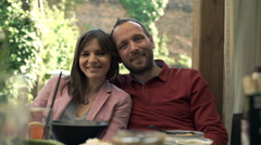 Portrait of happy couple sitting in cafe in the garden Stock Footage