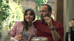 Young couple talking, eating and drinking in cafe in the garden Stock Footage