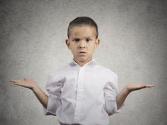 clueless child boy with arms out asking what's problem - stock photo
