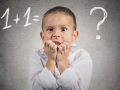 Confused, anxious boy trying to solve math problem Stock Photos