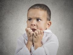 nervous anxious stressed child boy biting fingernails - stock photo