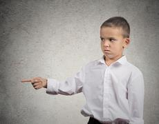 Unhappy boy pointing finger at someone, something - stock photo