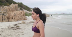 Young woman happy after jogging on the beach at cloudy weather. Fitness. Slow - stock footage