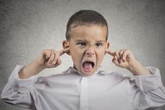 Angry pissed off boy plugs his ears with fingers Stock Photos