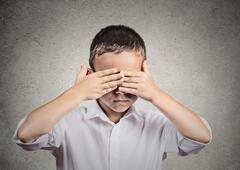 Boy covers his eyes with hands. Hear no evil concept Stock Photos