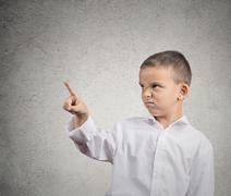 Unhappy boy pointing with finger at copy space - stock photo