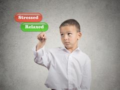 Boy pushing relaxed button mode on touch screen dispaly - stock photo