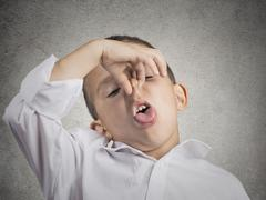Boy disgust on face pinches nose something stinks Stock Photos