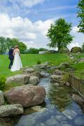 groom and bride walking on the grasss near the river - stock photo