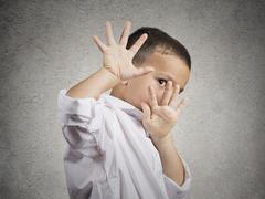child boy looking scared trying to protect himself - stock photo