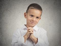 Boy gesturing with clasped hands, pretty please with sugar on top - stock photo