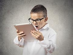 Shocked, frustrated boy using pad computer Stock Photos
