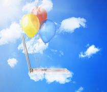 laptop computer with colorful balloons flying high in blue sky - stock photo