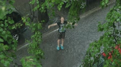Teen girl having fun in the rain. 4K UHD - stock footage