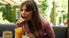 Happy, young woman drinking juice sitting in cafe in the garden Stock Footage